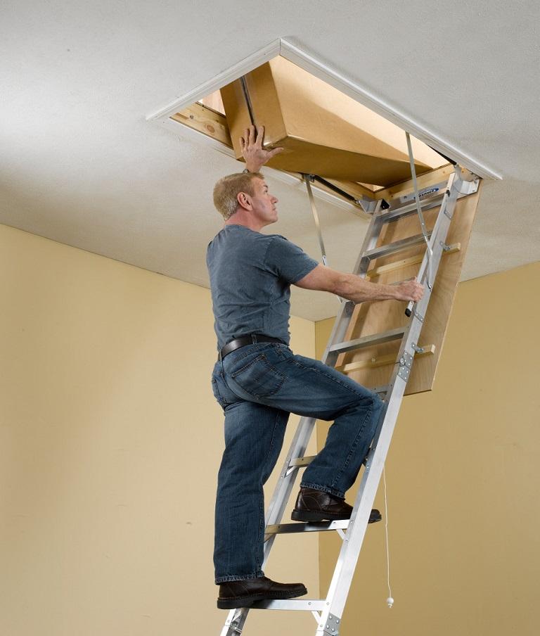 Man climbing a Werner AH2510 aluminum attic ladder