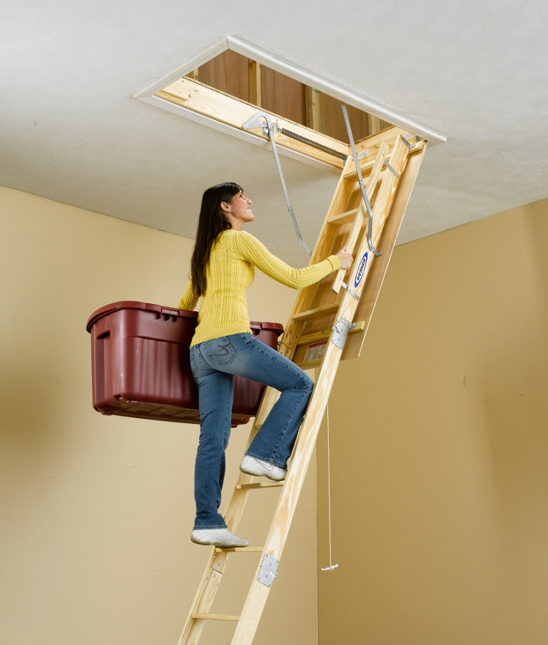 Woman climbing a Werner wood attic ladder